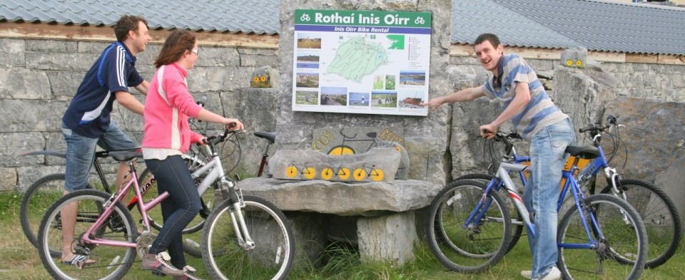 A Photo of cyclists viewing the map on a stone sign